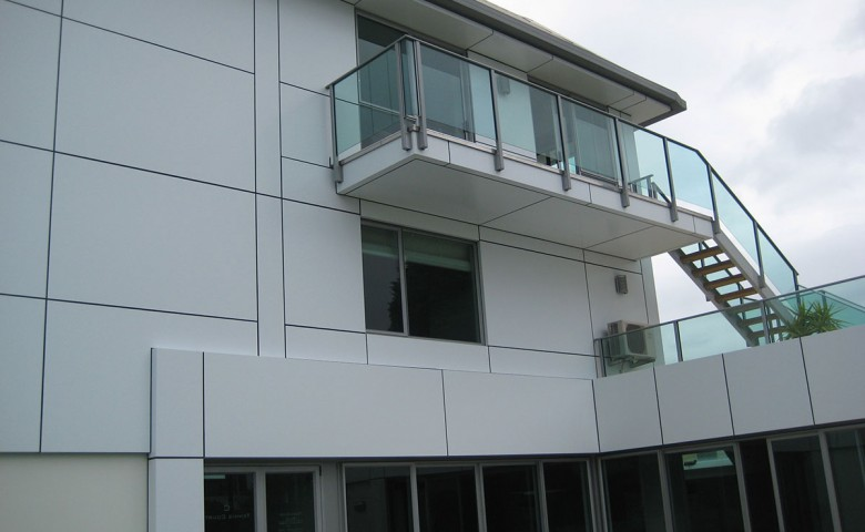 Glass balcony on white tiled cutterscove building project managed by IPMS